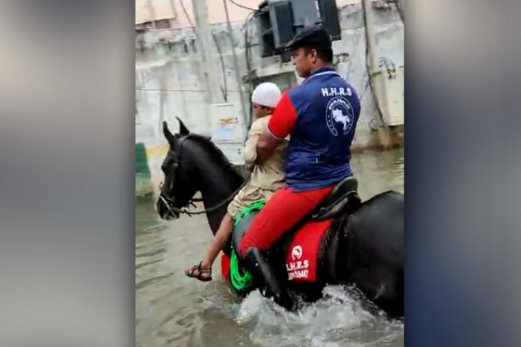 A horseman rescuing a kid from a flooded area in Toli Chowki
