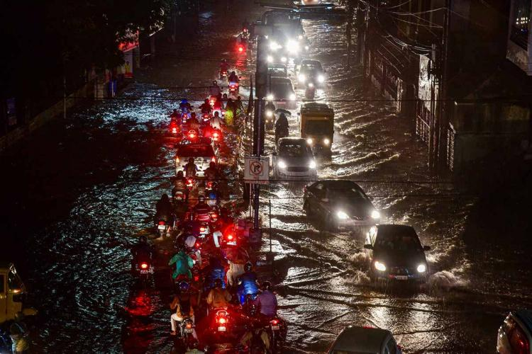 Vehicles ply on a waterlogged street in Hyderabad Saturday Oct 17 2020