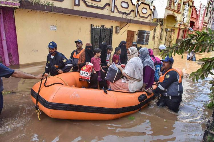 Disaster relief personnel are seen rescuing group of people from floods in an orange coloured boat