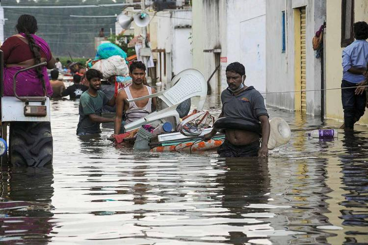 A man wades through flooded street in Hyderabad