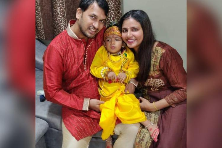 Ayaansh, dressed in Krishna's costume, seated between his parents