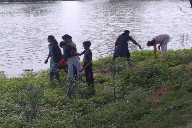 A lake in Hyderabad in which a group of children are playing at the bund