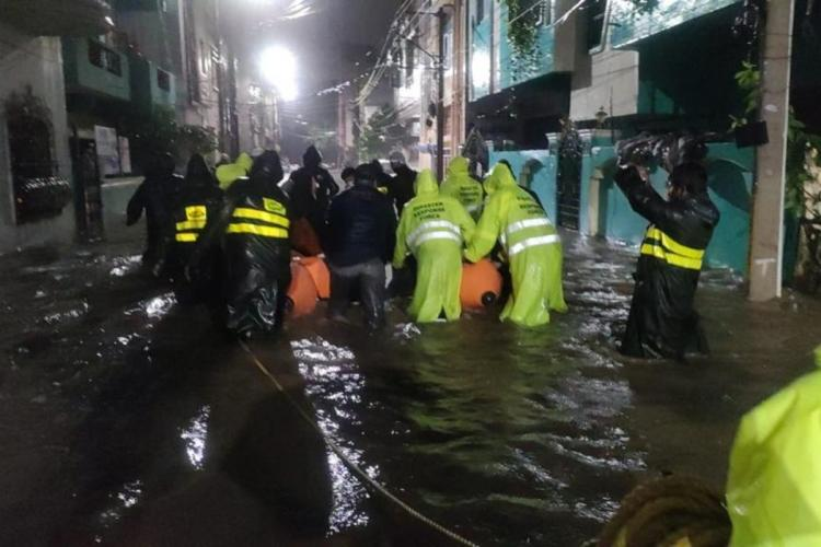 Rescue team evacuating residents through flooded roads on a boat