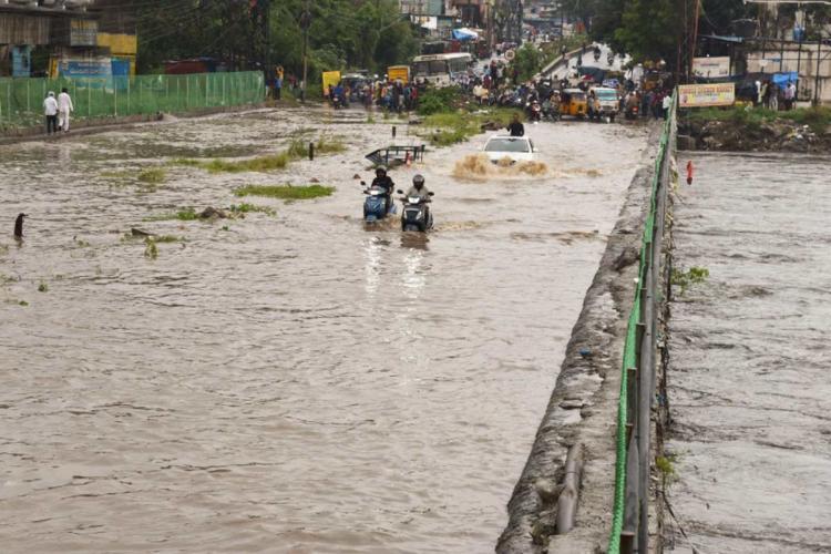 Two motorists crossing a flooded bridge