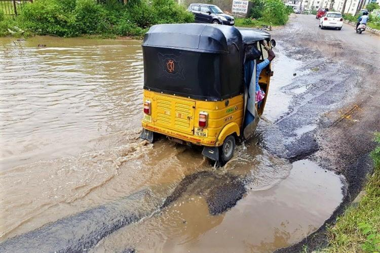 An auto moving on a waterlogged road
