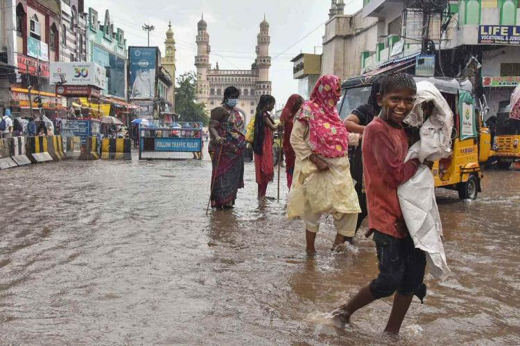 Commuters walk on a waterlogged street near the Charminar during rainfall