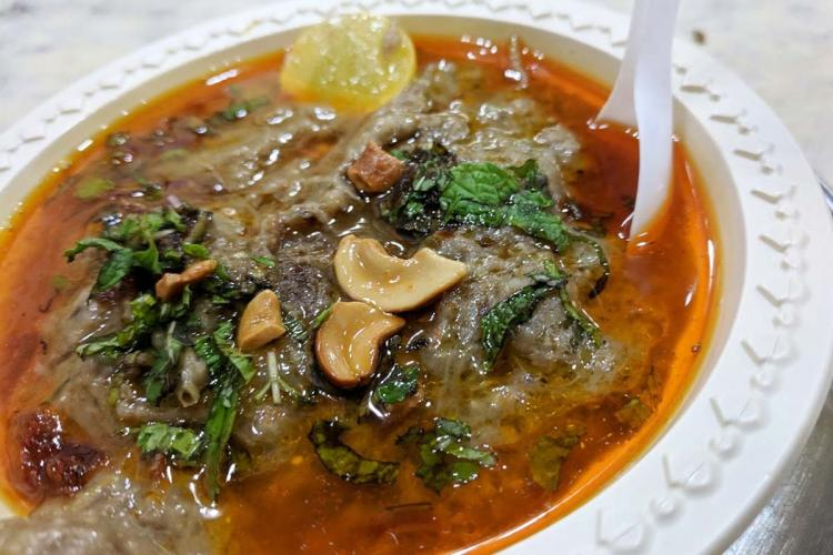 A plate of Haleem garnished with fried onion cashews and onion