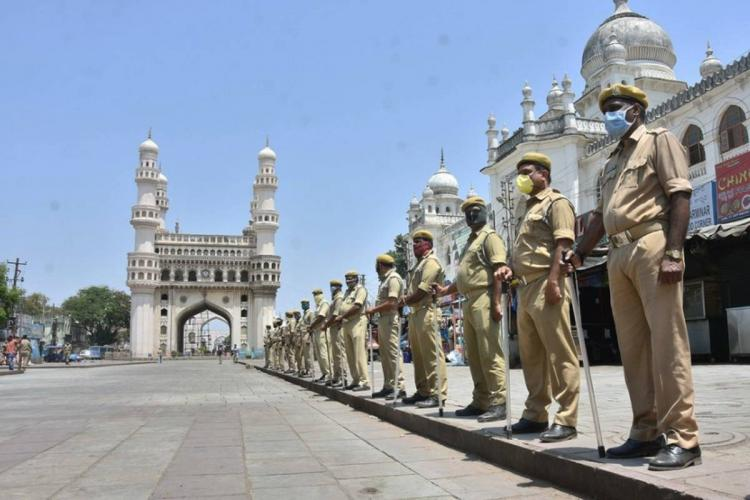 Telangana lockdown: A queue of policemen standing by the footpath with the Charminar in the background