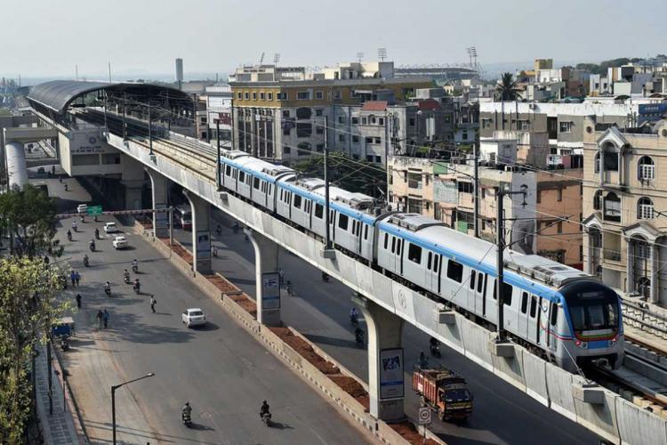 A Hyderabad metro train runs on an elevated railway line at Habsiguda in Hyderabad