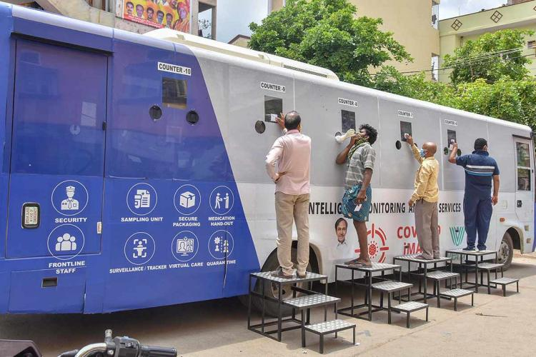 People stand on platforms next to a mobile coronavirus testing vehicle in Hyderabad where samples are being collected