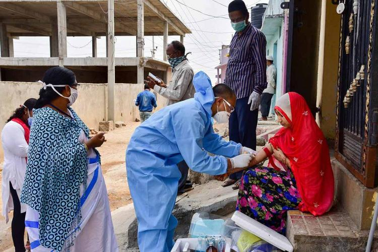Health workers examining a woman sitting in front of a house and wearing a red scarf