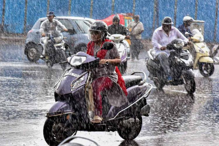 A woman rides her bike in the downpour