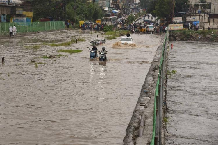 People in two wheelers cars and buses travelling in knee deep water in Hyderabad