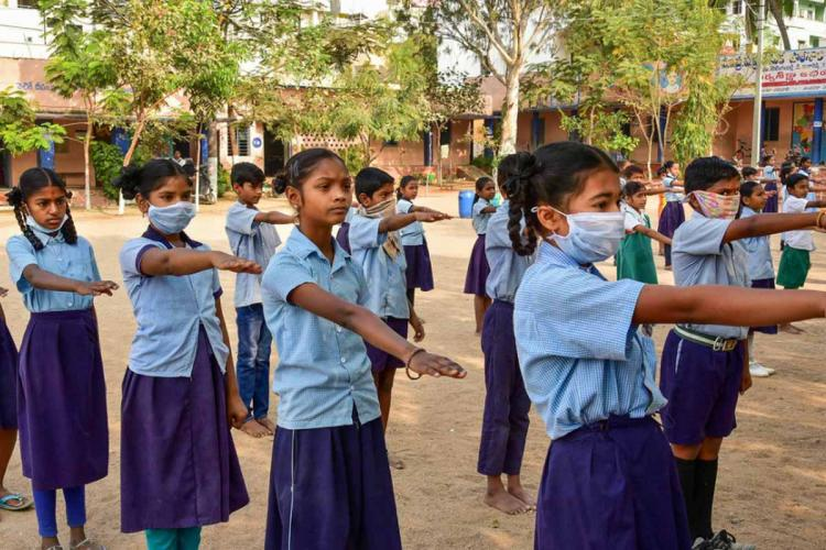 A file image of students seen wearing masks as prevention against coronavirus during school assembly in Hyderabad