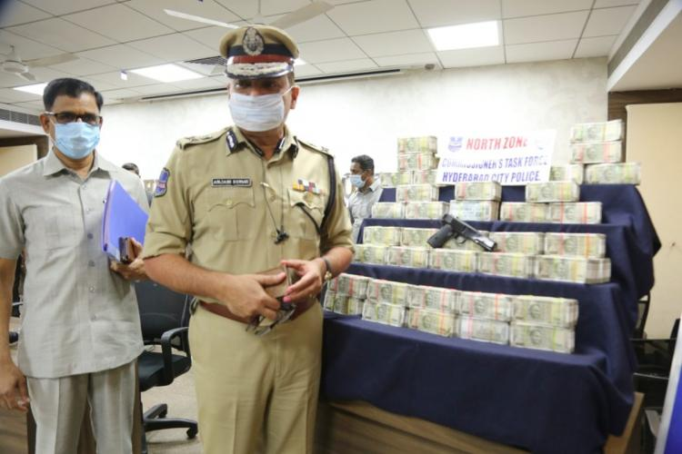 Hyderabad police commissioner posing against the seized items