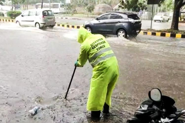 A worker from the Disaster Response Force clearing the drains