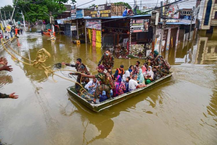 People being evacuated in a boat in the rains from a flooded area