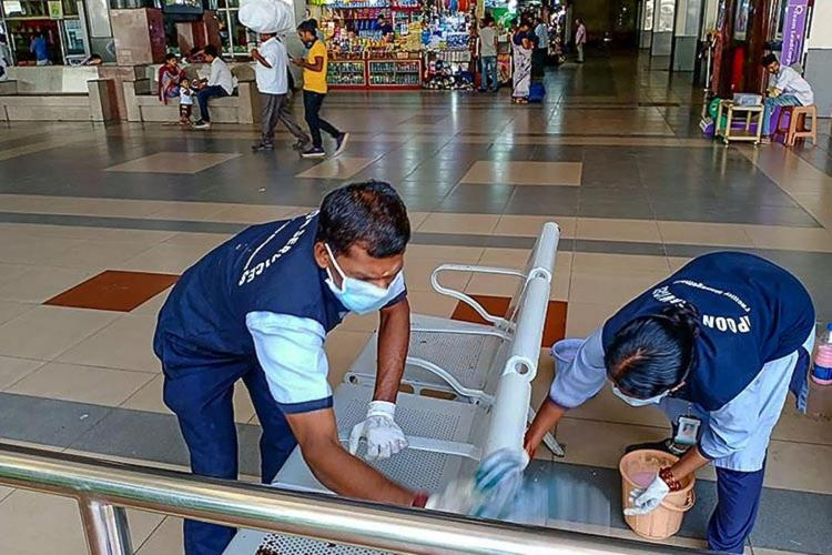 Sanitary workers cleaning seats at a metro station