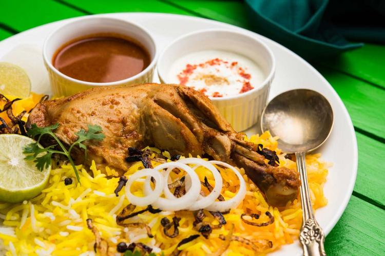A plate of chicken biriyani with raita and other side accompaniments