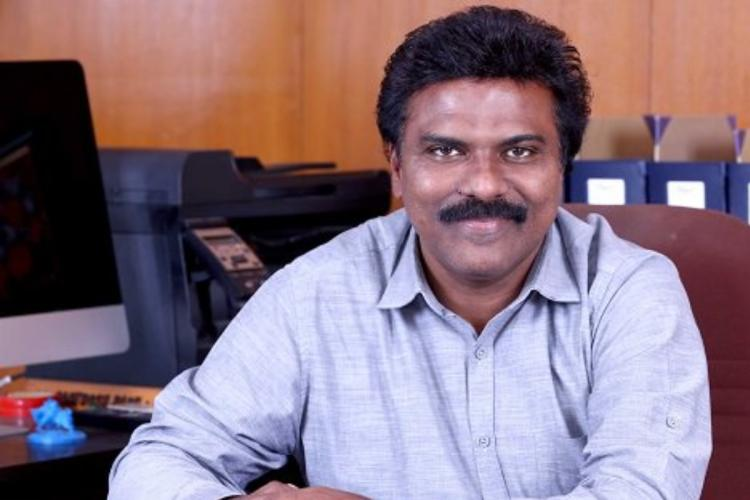 Former IAS officer Santhosh Babu seated with a blue shirt at his desk