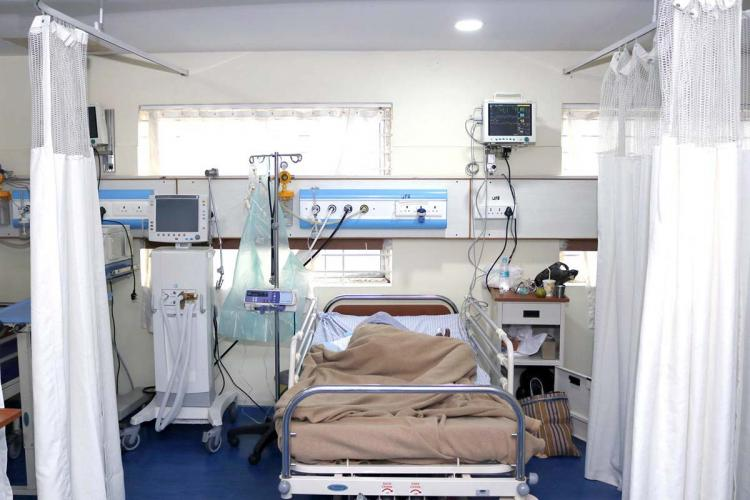 An ICU bed in an Indian hospital with a patient sleeping on his side