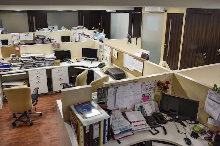 Cubicles arranged within an office with files and folders lying around