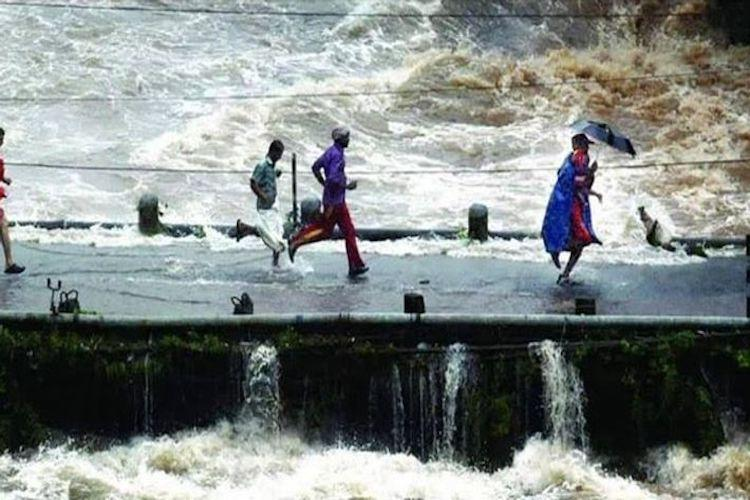 Watch Dramatic video of rescue officer running with child through flooding Kerala bridge