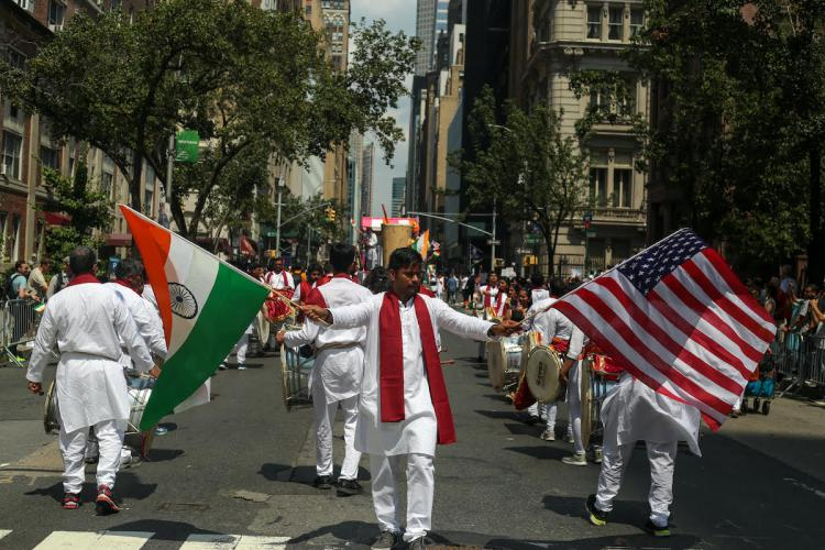 Independence Day parade in Manhattan a man in a white kurta and red scarf holding US and India flags