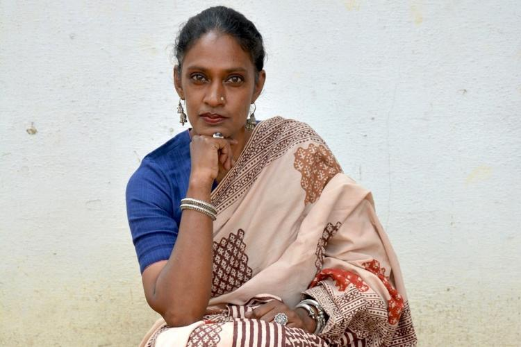 Woman wearing a light pink woven saree from the India Handmade Collective with a blue blouse and posing for a photo