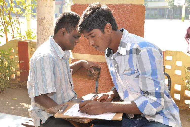 A scribe writing exam for a student with visual impairment in Andhra Pradesh