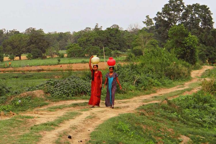 Two women carrying pots walk down a path in a village in south India