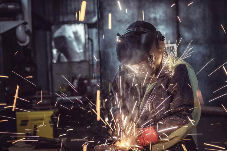 Sparks fly as an industrial worker wearing protective uses a machine