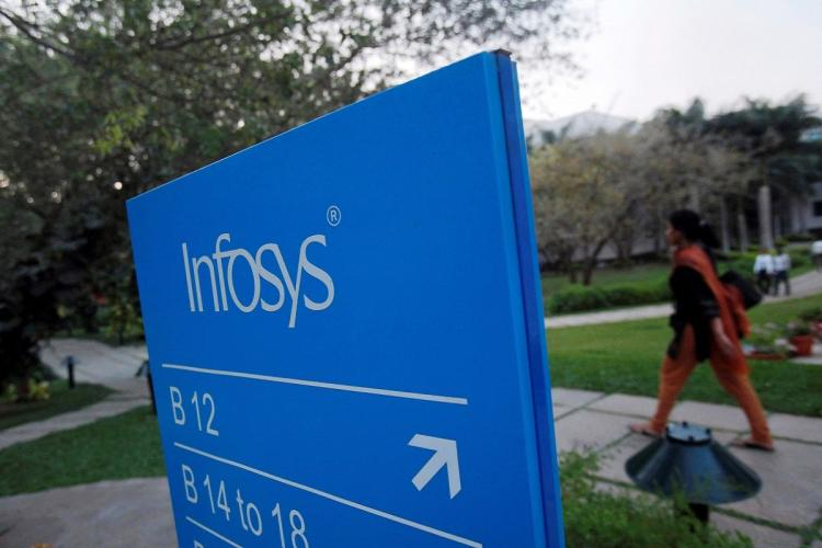 Infosys logo at company with an employee working in the background