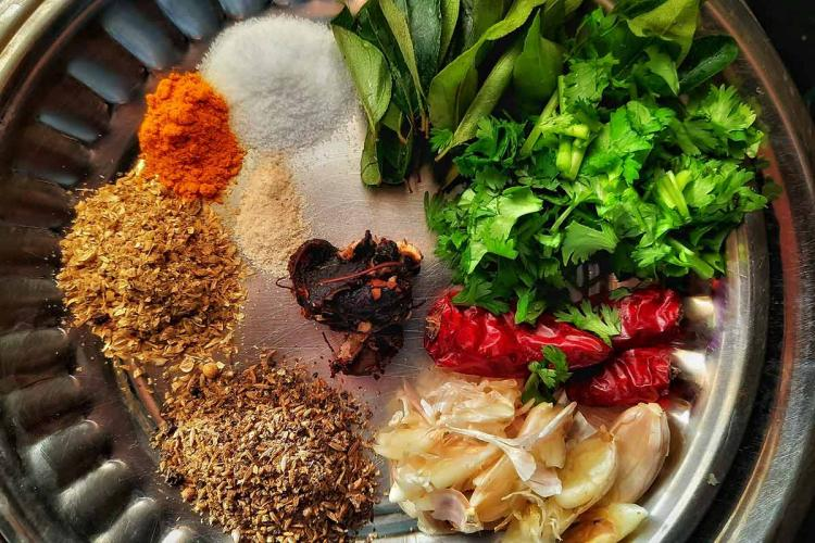 A plate of spices and fresh herbs and ingredients to make a rasam