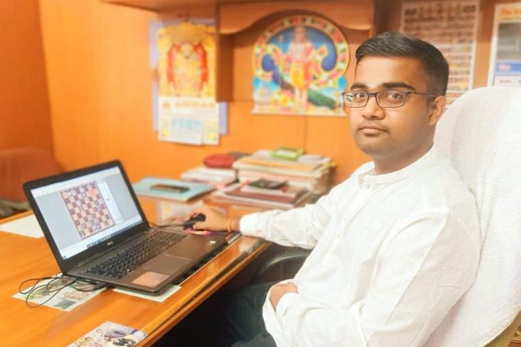 Chess grandmaster P Iniyan at his desk with chess game seen on laptop