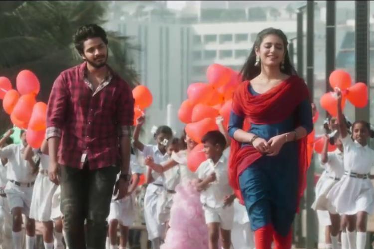 Screenshot from Trailer of Ishq where Teja Sajja is walking behind Priya Prakash Varrier with school children in uniforms behind them holding red balloons