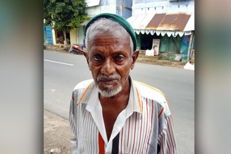 81-year-old Kerala man named Ismailkutty looks unsmiling at the camera. He is wearing a white striped shirt and a green cloth cap, and standing by the side of a street.