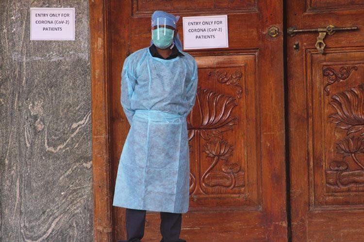 A doctor in PPE gear standing against the COVID-19 ward door