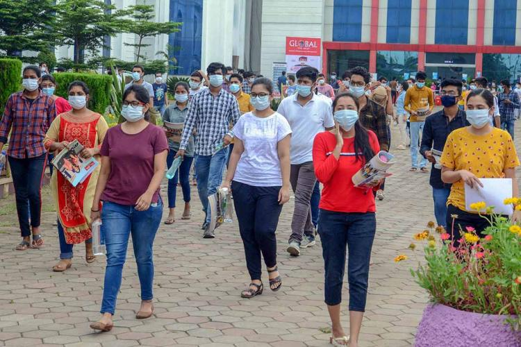 Students wearing masks walking up to a JEE test centre