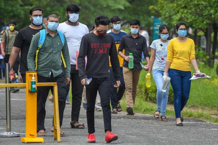 A group of JEE candidates are seen in this image. They are wearing masks and gloves.