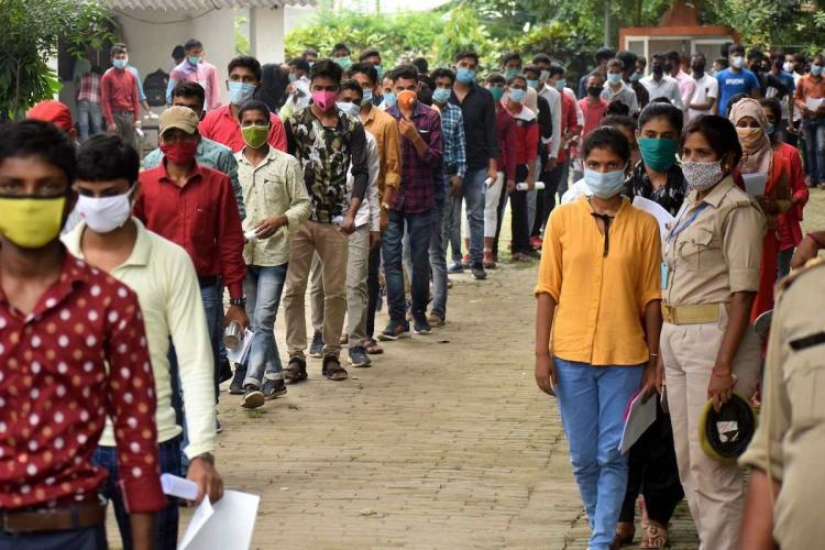 Students in line waiting to enter the exam centre for JEE in 2020 They are wearing masks and are delayed due to checks