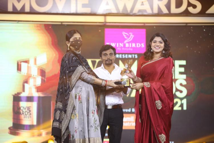 Aparna Balamurali is seen in a red saree and is seen receiving the award