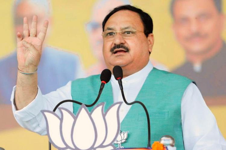BJP Chief J P Nadda seen wearing a sea green coloured jacket and addressing a gathering from a mike