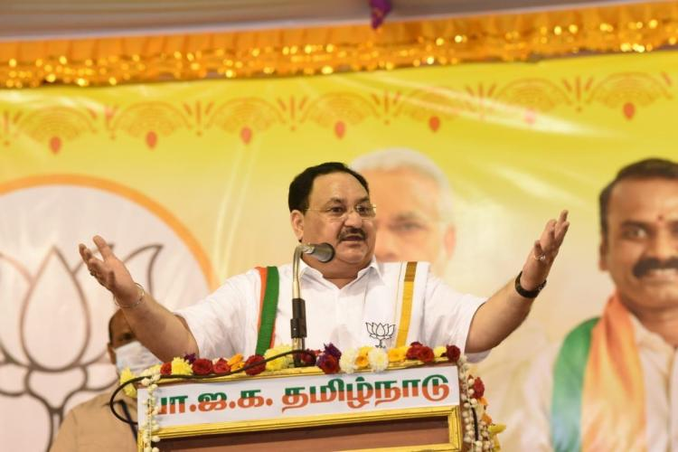 JP Nadda addressing a public meeting in Chennai standing at a podium in front of a mic with his arms spread wide