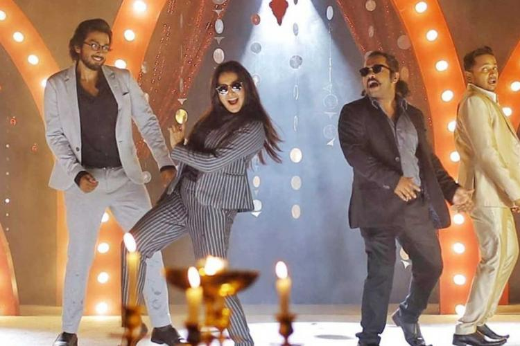 Four people dance on a lighted stage wearing suits, one of them is Manju Warrier