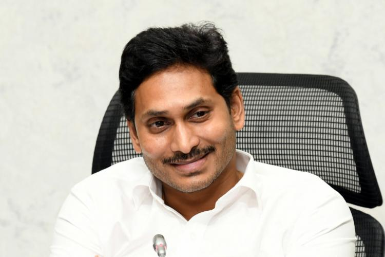 CM Jagan dressed in a white shirt smiling looking away from the camera
