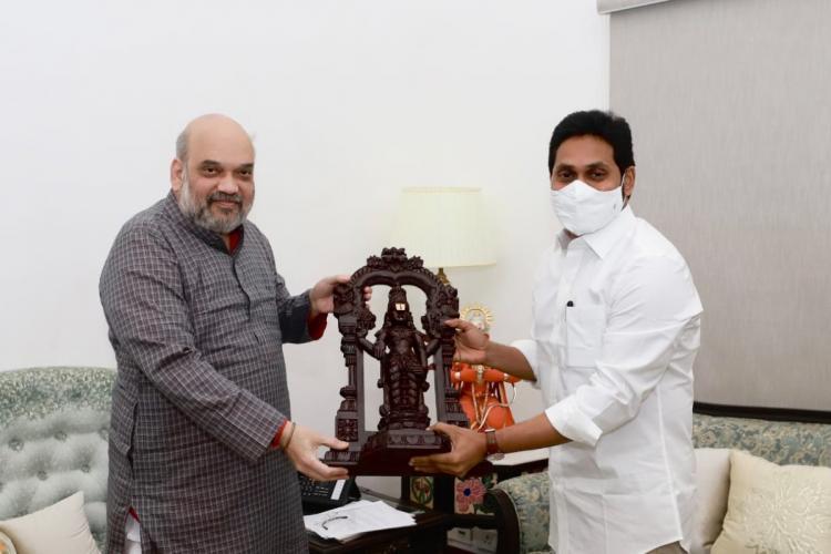 Amit Shah and Jagan holding an idol of Venkateswara deity Jagan is wearing a mask and presentign the idol ro Shah