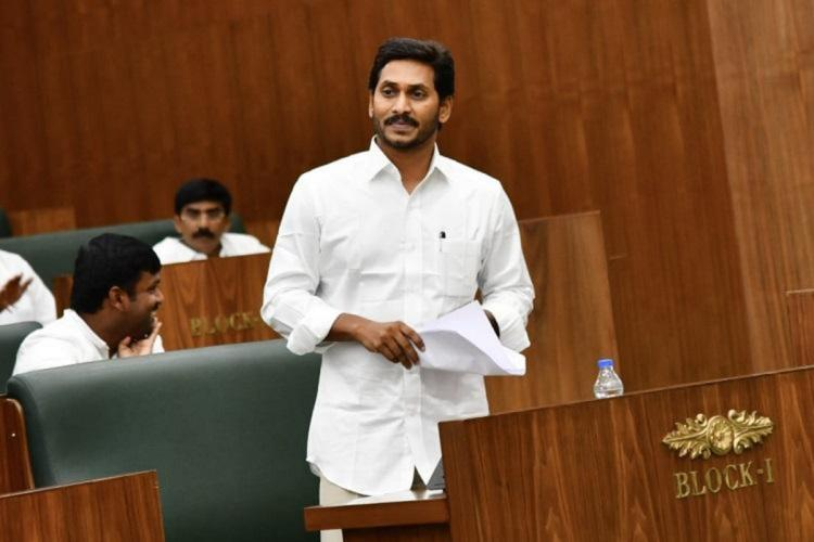 Andhra Pradesh Chief Minister Jagan Mohan Reddy wearing a white shirt standing in the Assembly