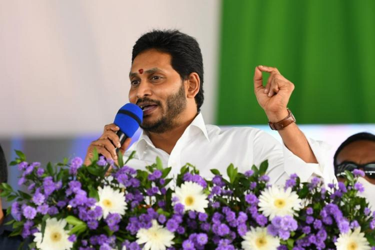 Andhra Pradesh Chief Minister Jagan Mohan Reddy wearing a white shirt speaking on a stage into of a mic
