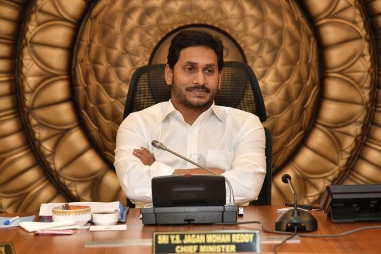 Andhra Pradesh Chief Minister Jagan Mohan Reddy wearing a white shirt sitting at his desk in front of a mic with his official name plate in front of him against a backdrop of golden circles